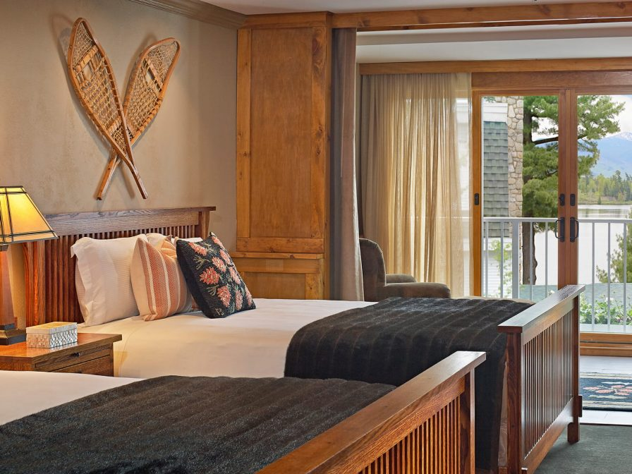 A guest room with two queen size beds and view of the lake