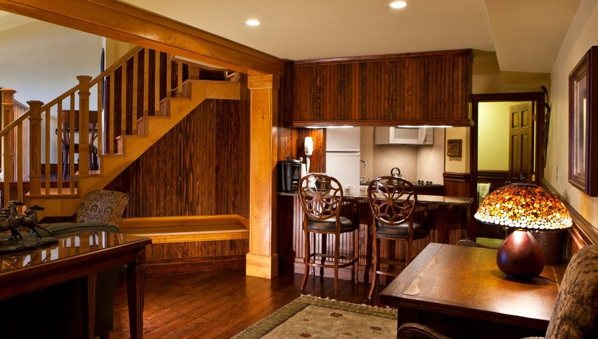 Large room with a small kitchen and staircase