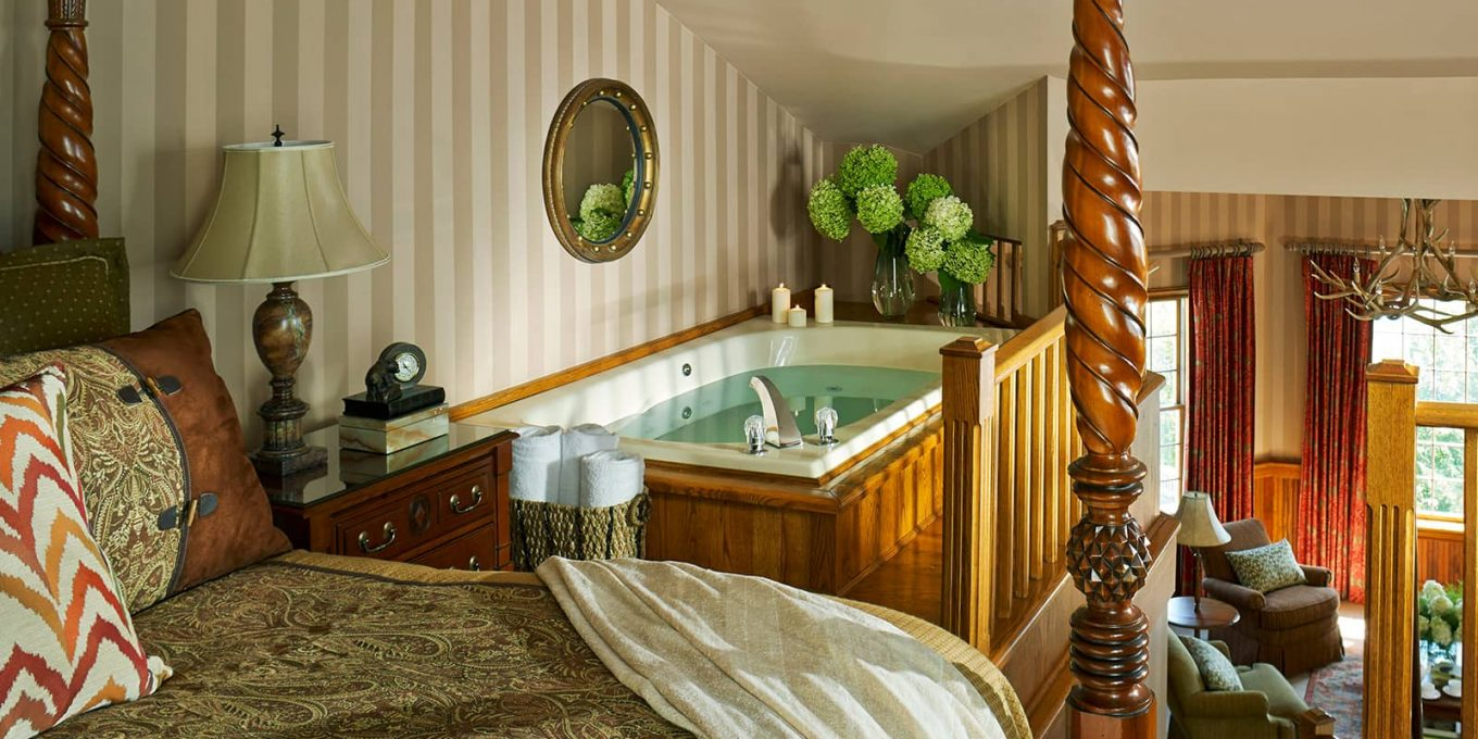 Room with a large poster bed and spa tub