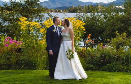 Newlyweds on grassy area in front of lake