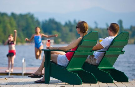 Parents sitting on green Adirondack chairs by the lake