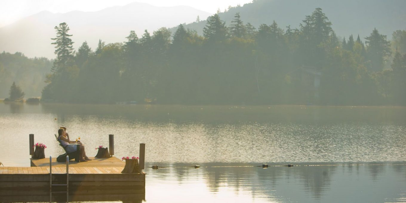 A couple reclining on a dock overlooking a lake with mountain backdrop