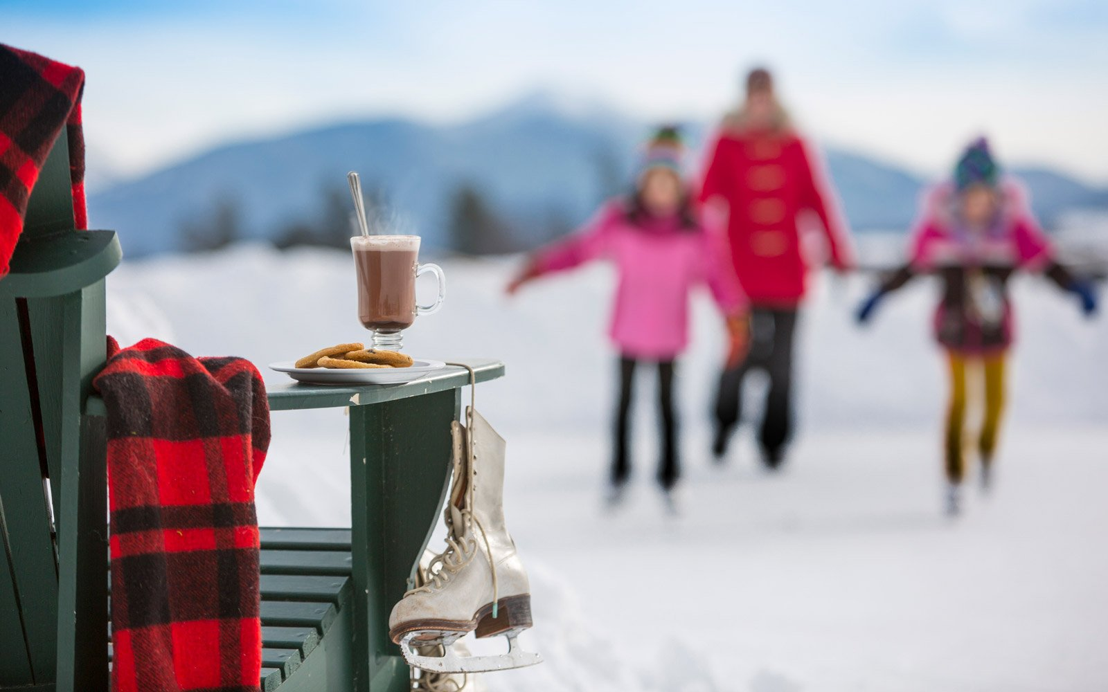 Hot chocolate on a chair and a family ice skating