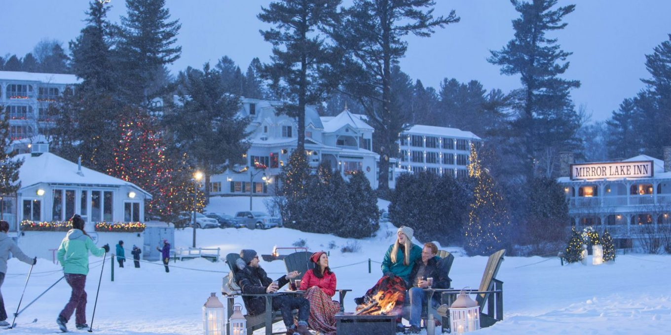 Couples sitting by the fire on the frozen lake