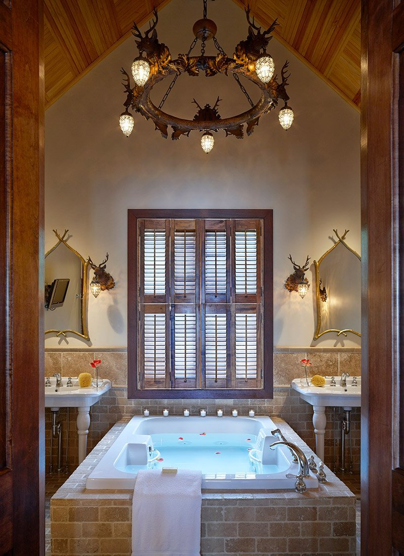 Large bathtub with chandelier above