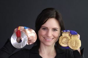 Andrea Henkel holding her Olympic and World Championship medals