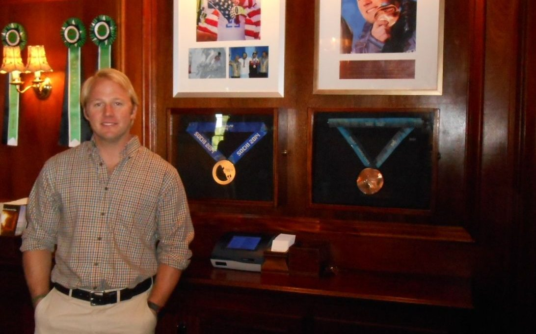 Andrew Weibrecht beside his displayed Olympic medals at the front desk of Mirror Lake Inn's Resort and Spa