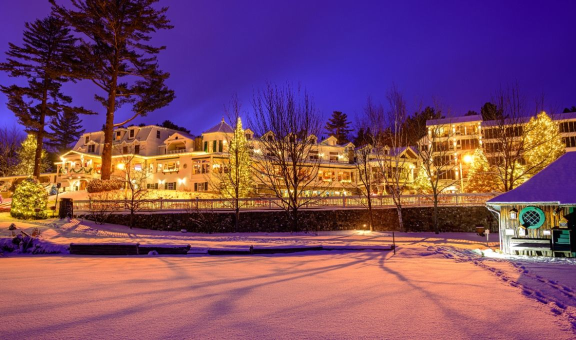 Mirror Lake Inn Resorts and Spa property with lights from the dock
