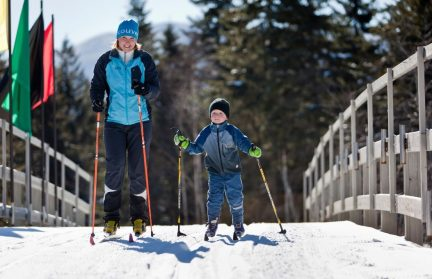 Mom and son cross country skiing on a bridge around Adirondacks