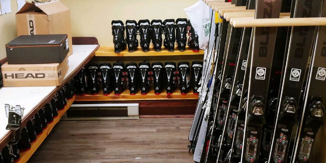 Ski equipment rental room with various boots and skis