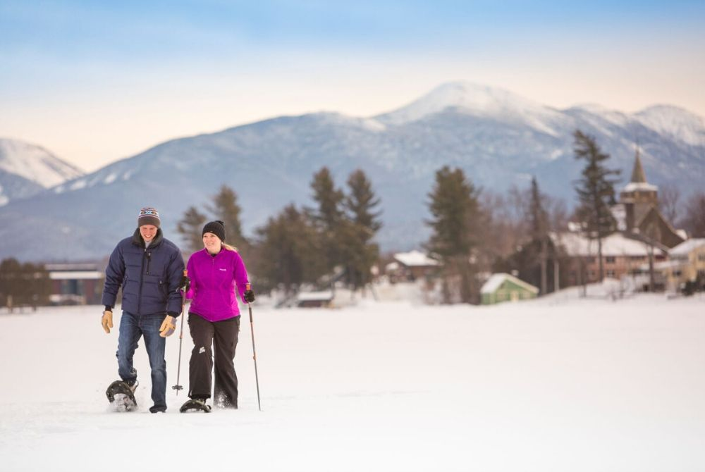 A male and a female snowshoeing on the frozen Mirror Lake