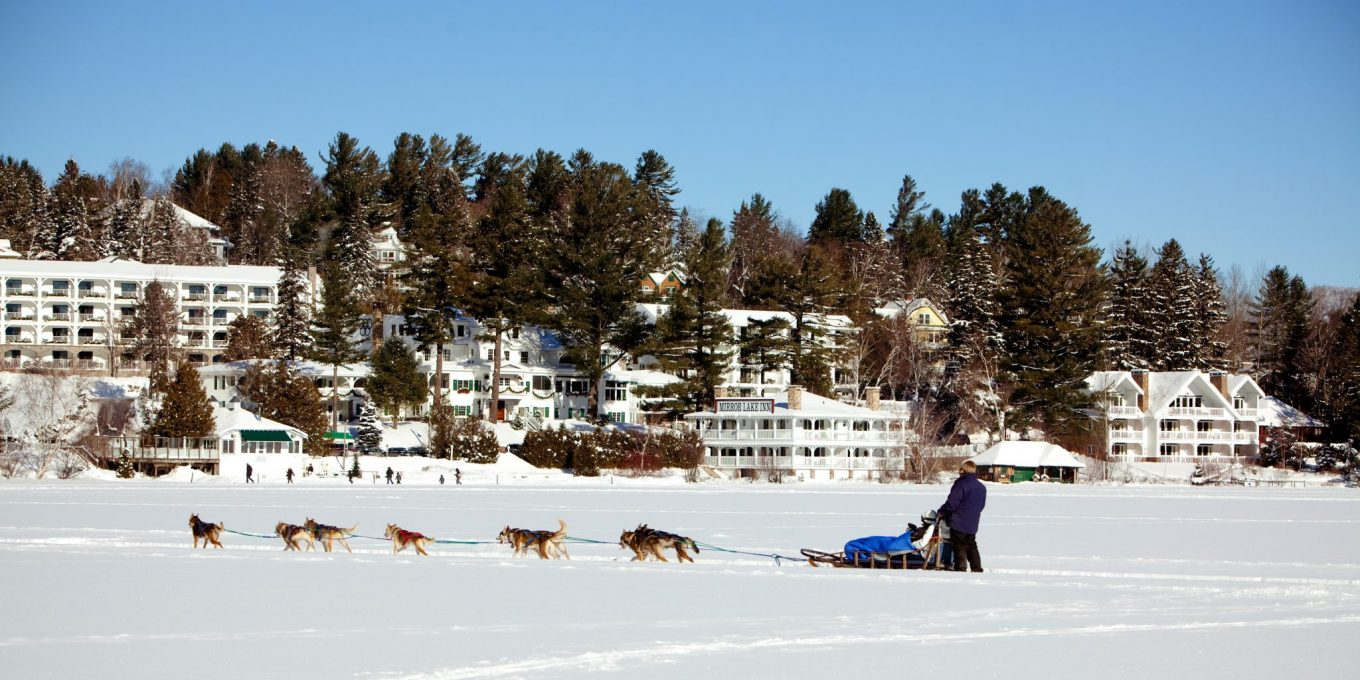 Dog sled moving in front of Mirror Lake Inn.