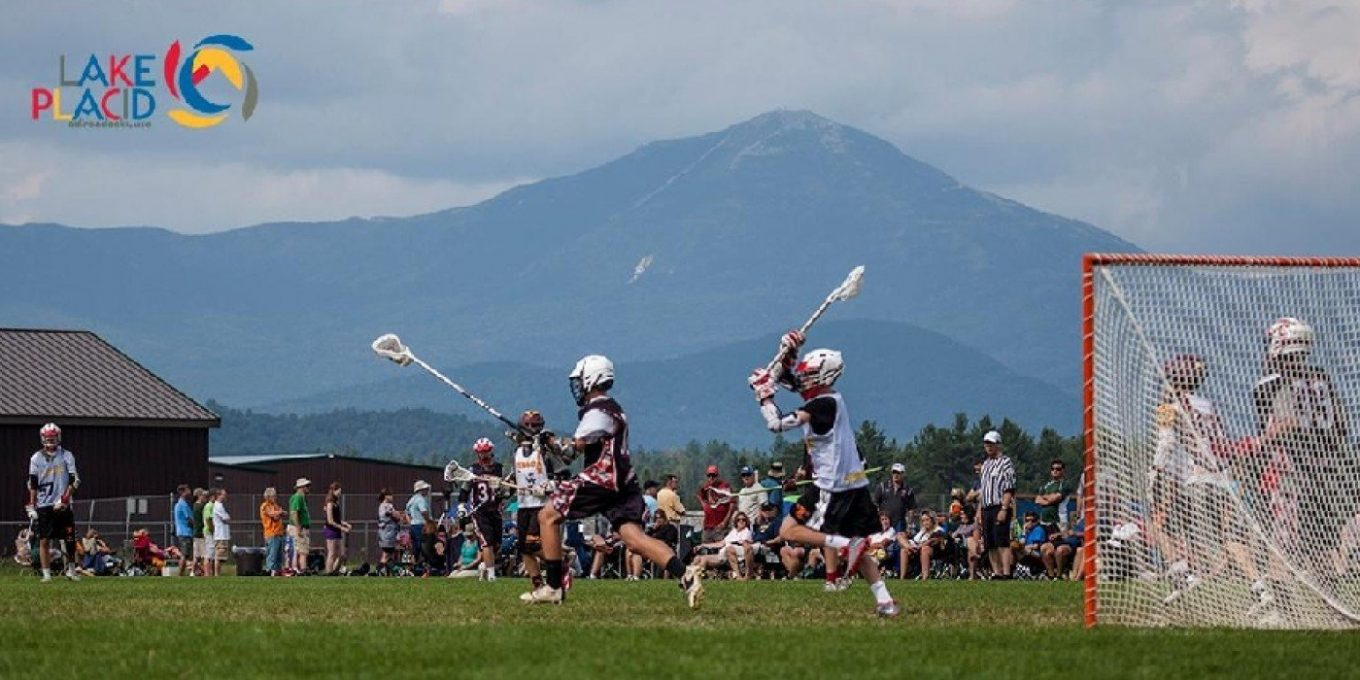Lacross players mid-game on a field with a mountain backdrop