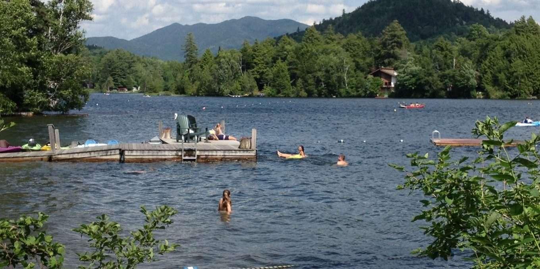 People swimming lakeside near a wooden dock.