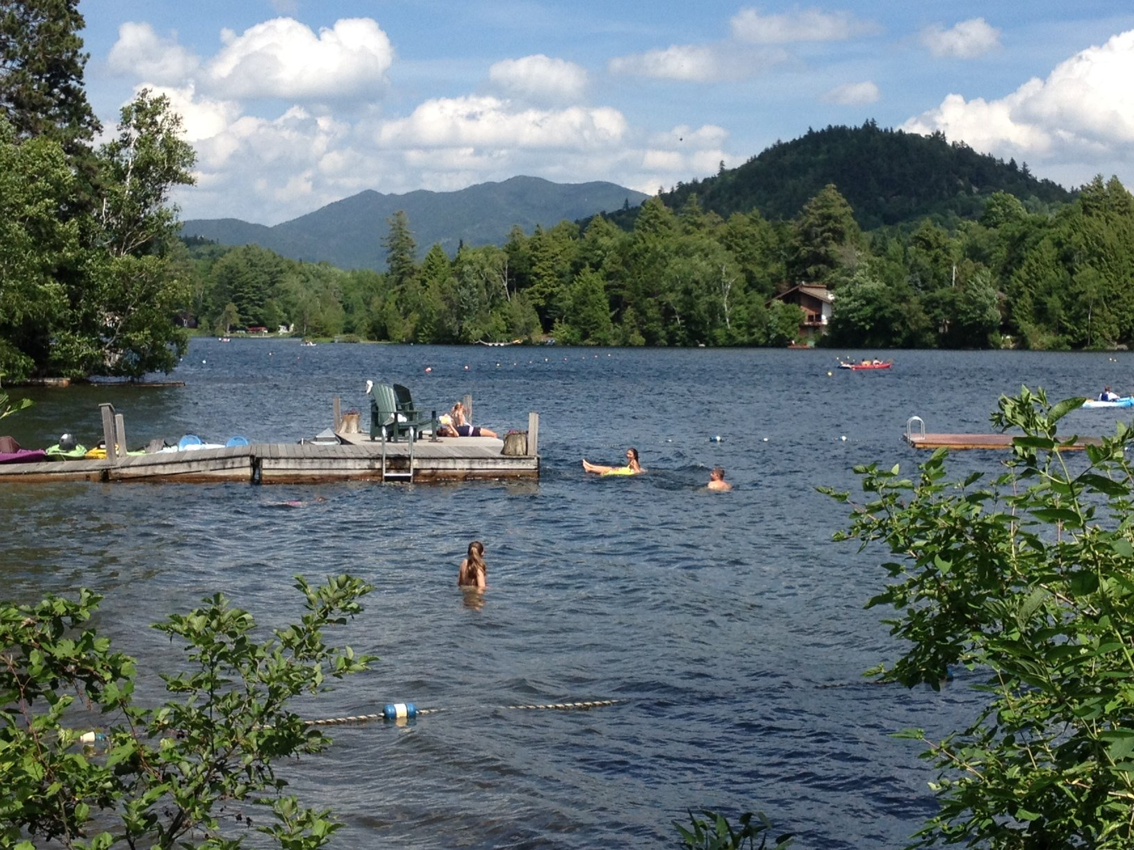 People swimming lakeside near a wooden dock.