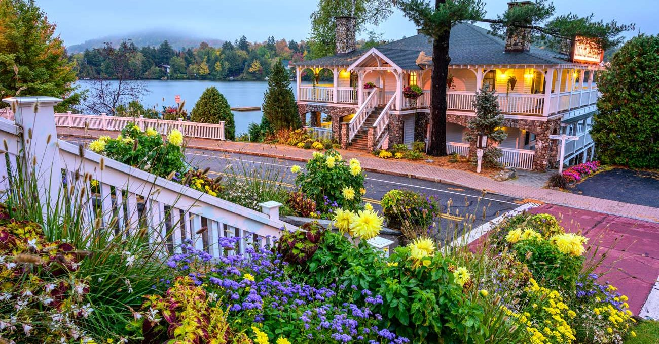 Main entrance of Mirror Lake Inn from across the road near summer flowers