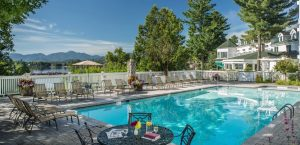 Mirror Lake Inn's outdoor swimming pool on a sunny day with a mountain view.