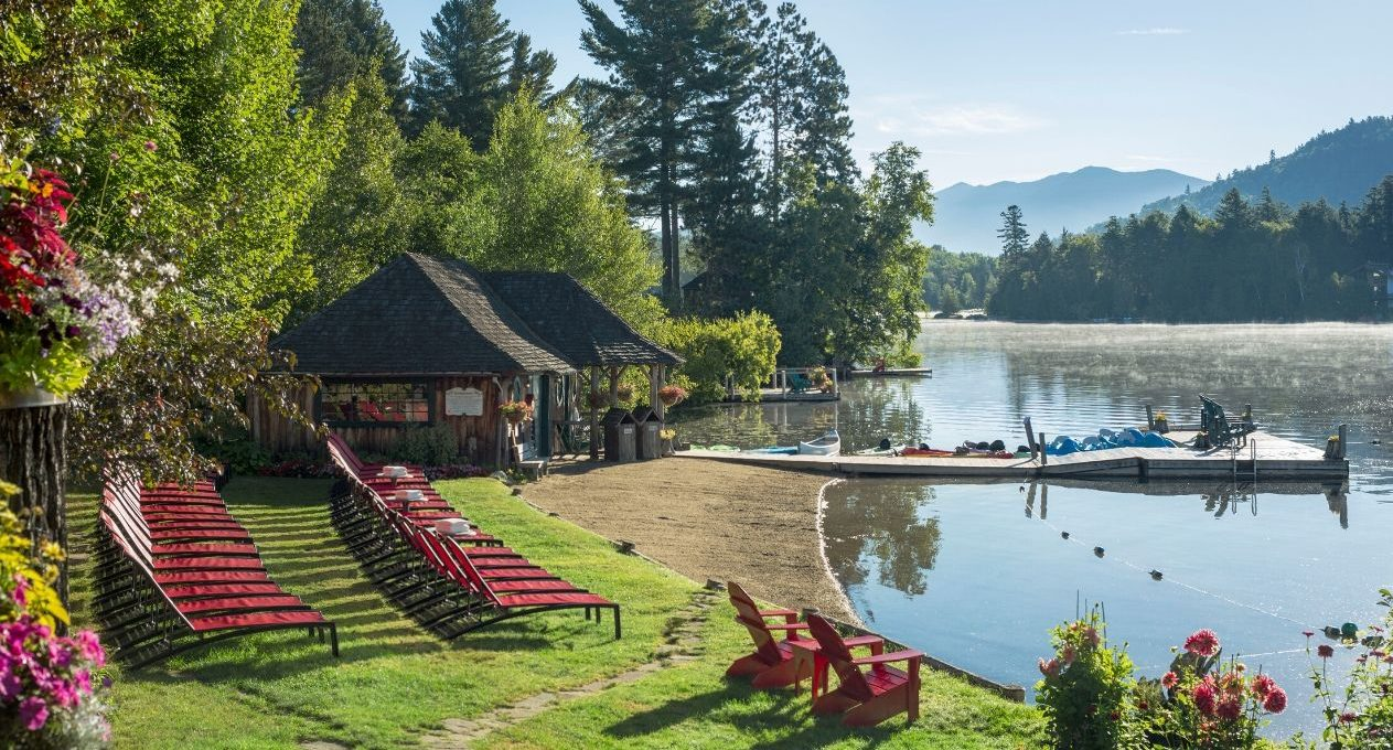 Mirror Lake Inn's private beach with lounge beach chairs, a cabin, and a dock.