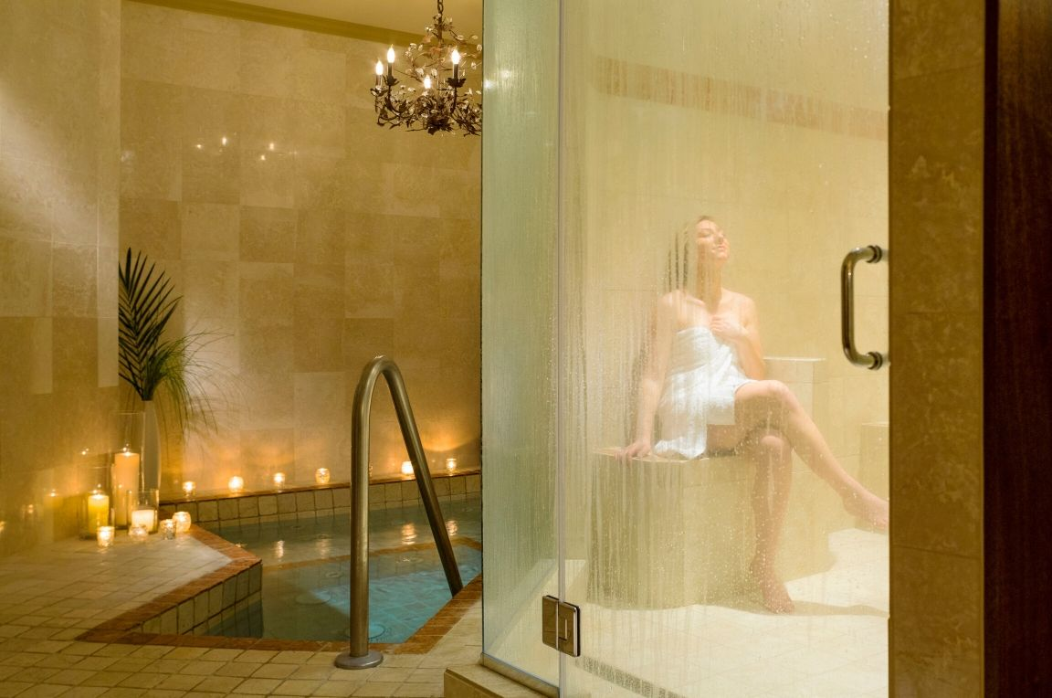 A woman inside the steaming room with a hot tube beside the room lighted with candles at Mirror Lake Inn's spa.