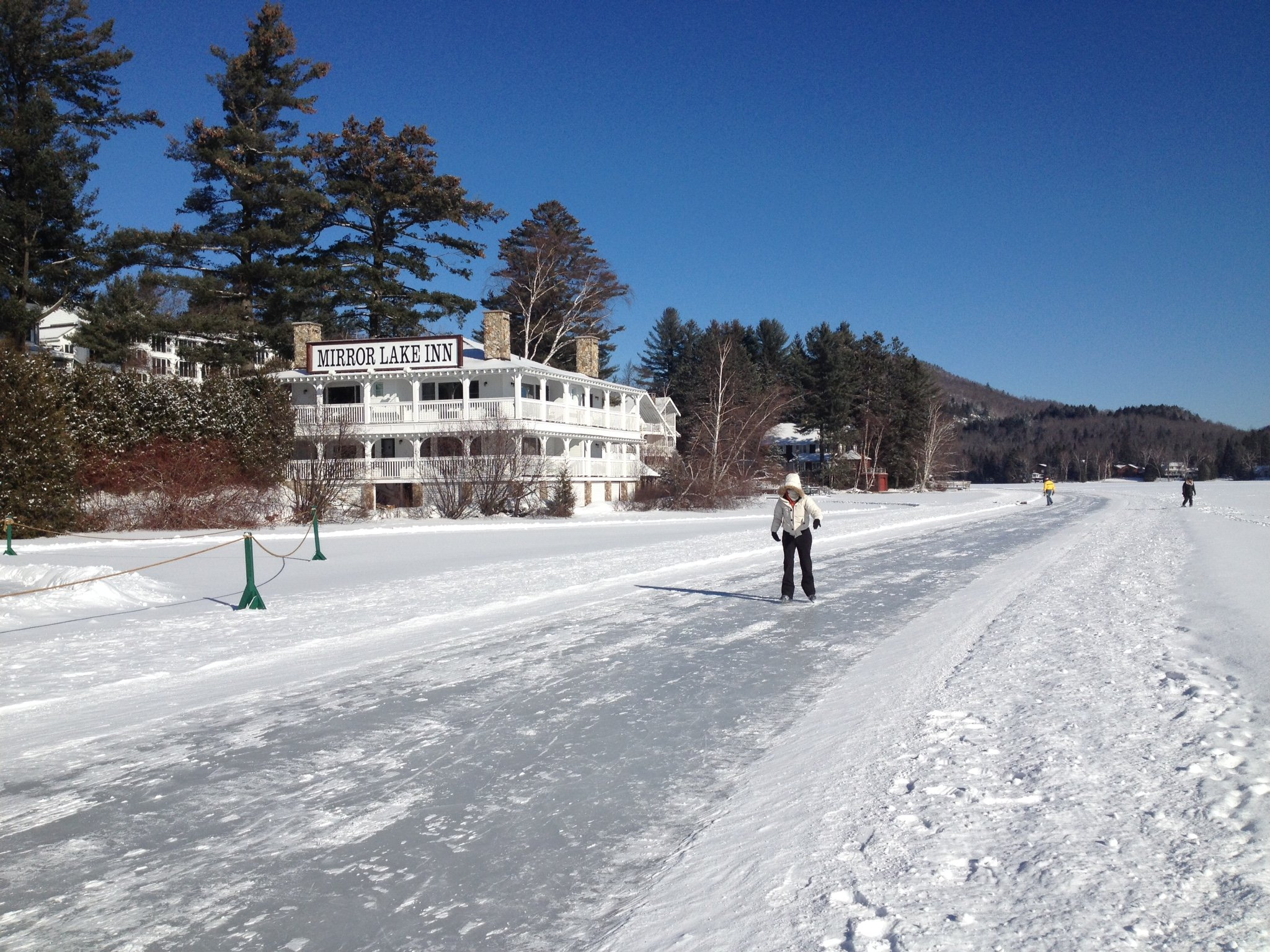 Woman skating solo on lake path in front of hotel