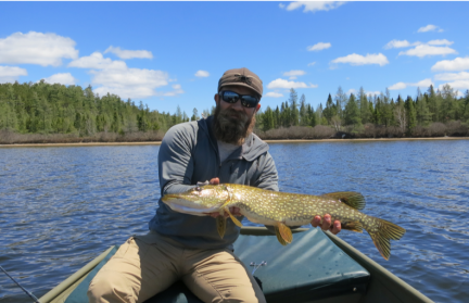 A bearded man holding a northern pike fish sitting in a boat on a lake