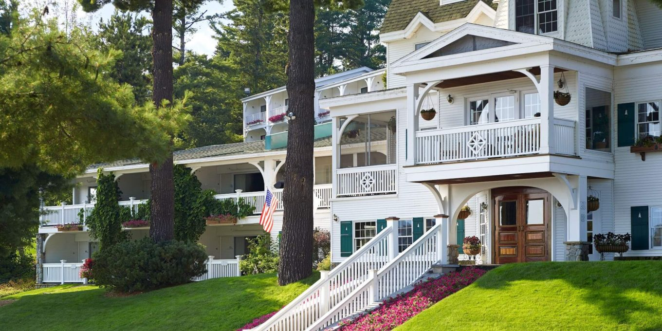 Front view of the Mirror Lake Inn with pink flower beds, green lawns and towering trees