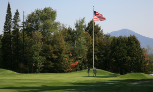Two people playing golf beside an American flag in Lake Placid
