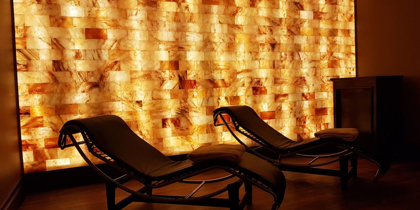 Reclining chairs silhouetted against a glowing salt therapy wall