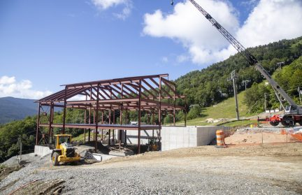 A building structure with metal beams on a mountainside next to a crane