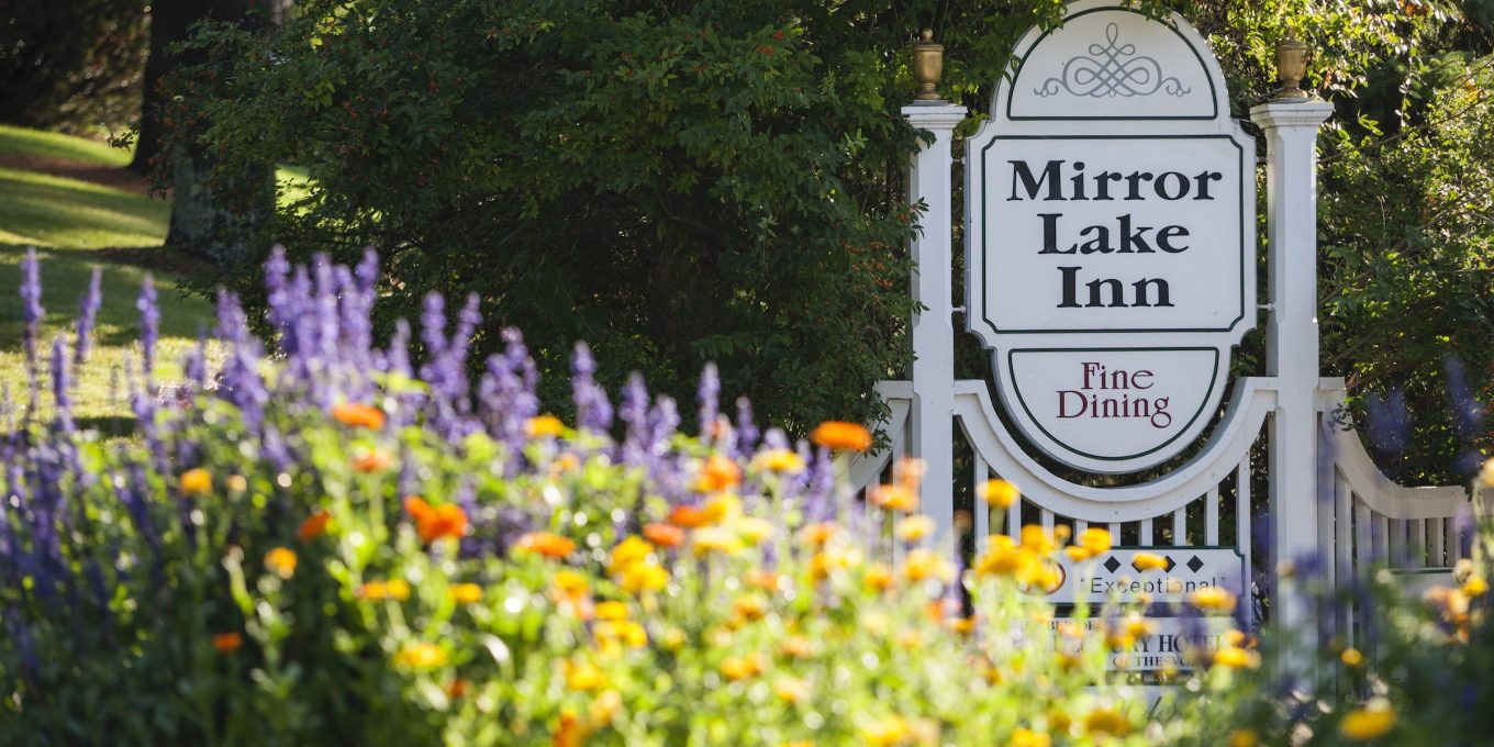 The Mirror Lake Inn signage with lavendar, orange and yellow flowers in the foreground