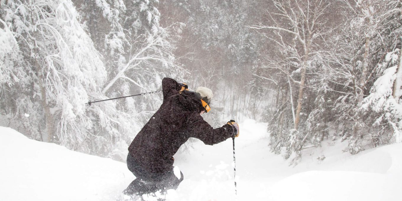 Man Skiing downhill with powder kicking up in front