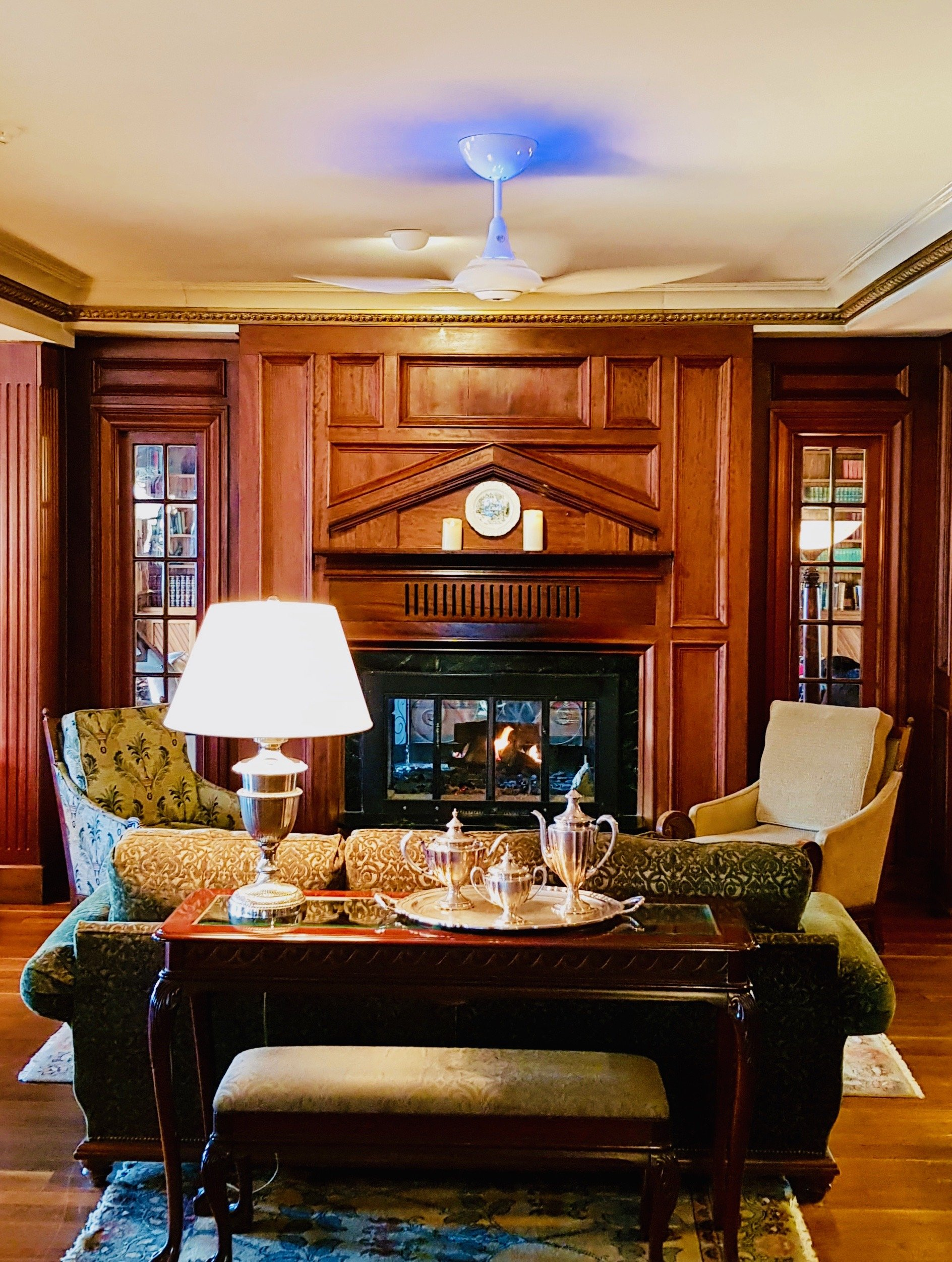 A wood-panelled lobby fireplace and seating area with a UV light ceiling fan