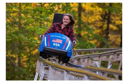 A woman in a red plaid shirt riding a single-person coaster outdoors