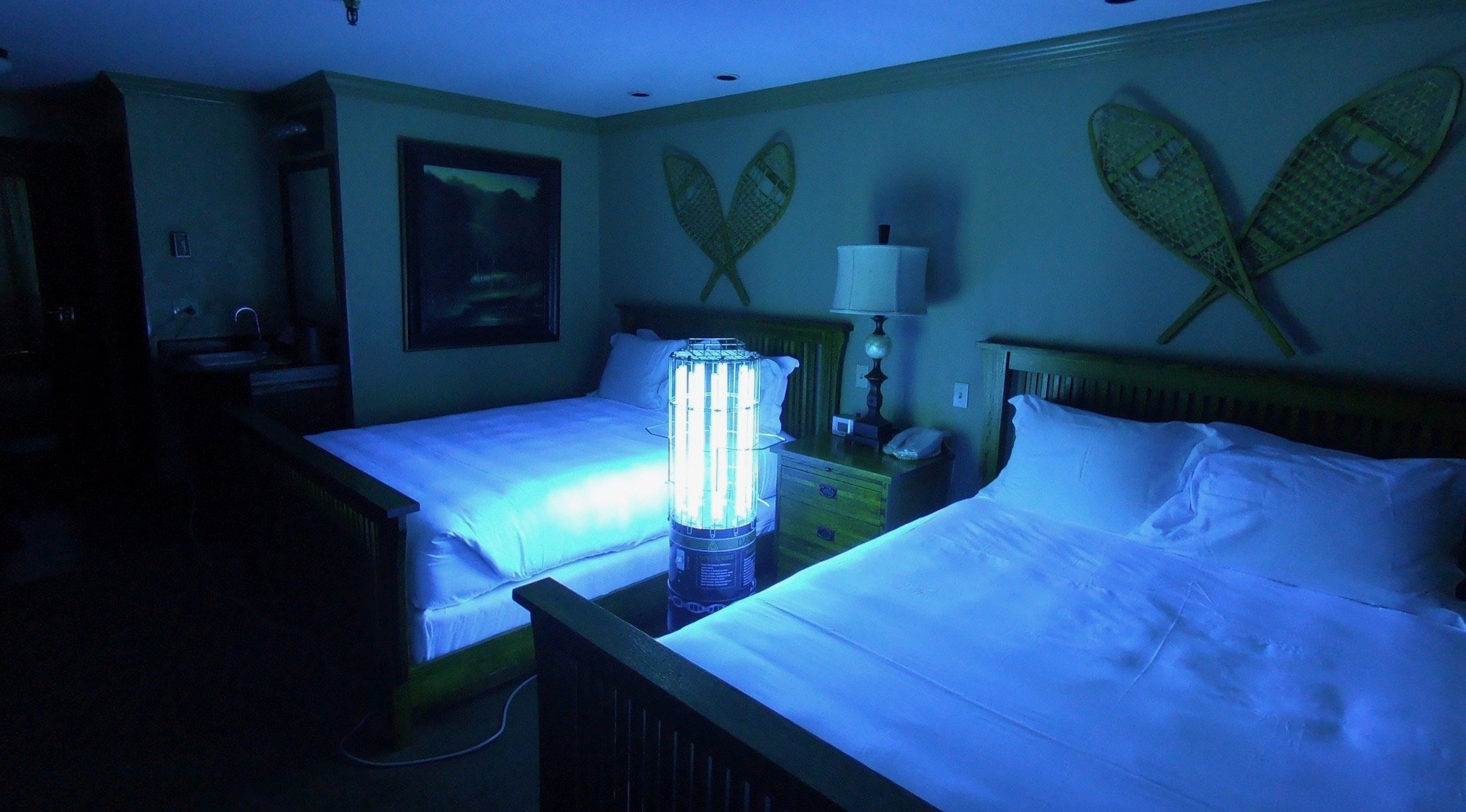A dark hotel room with two double beds lit by the blue light of a UV disinfection light