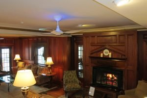 Wood-panelled hotel lobby seating area with a UV light ceiling fan