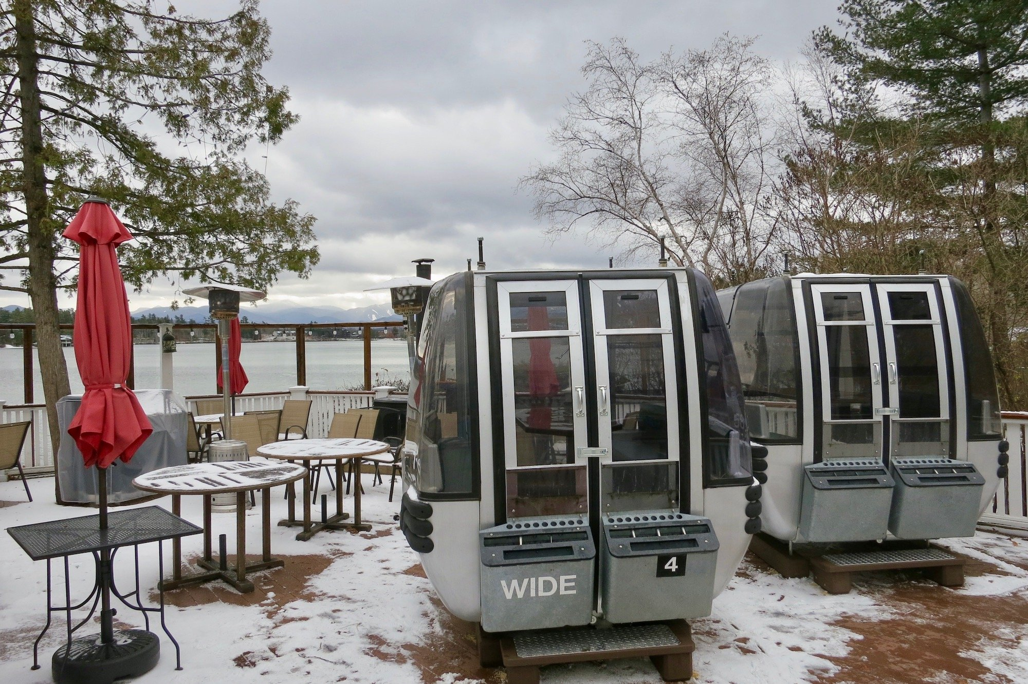A snowy outdoor eating area with two ski gondolas