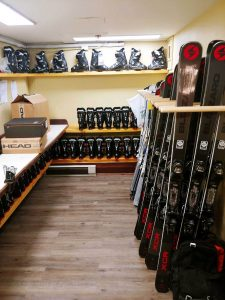 A ski equipment room containing black skis and black ski boots