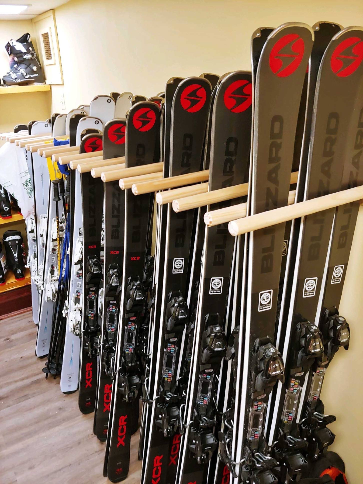 Multiple rental skis leaning against a wall in their holders