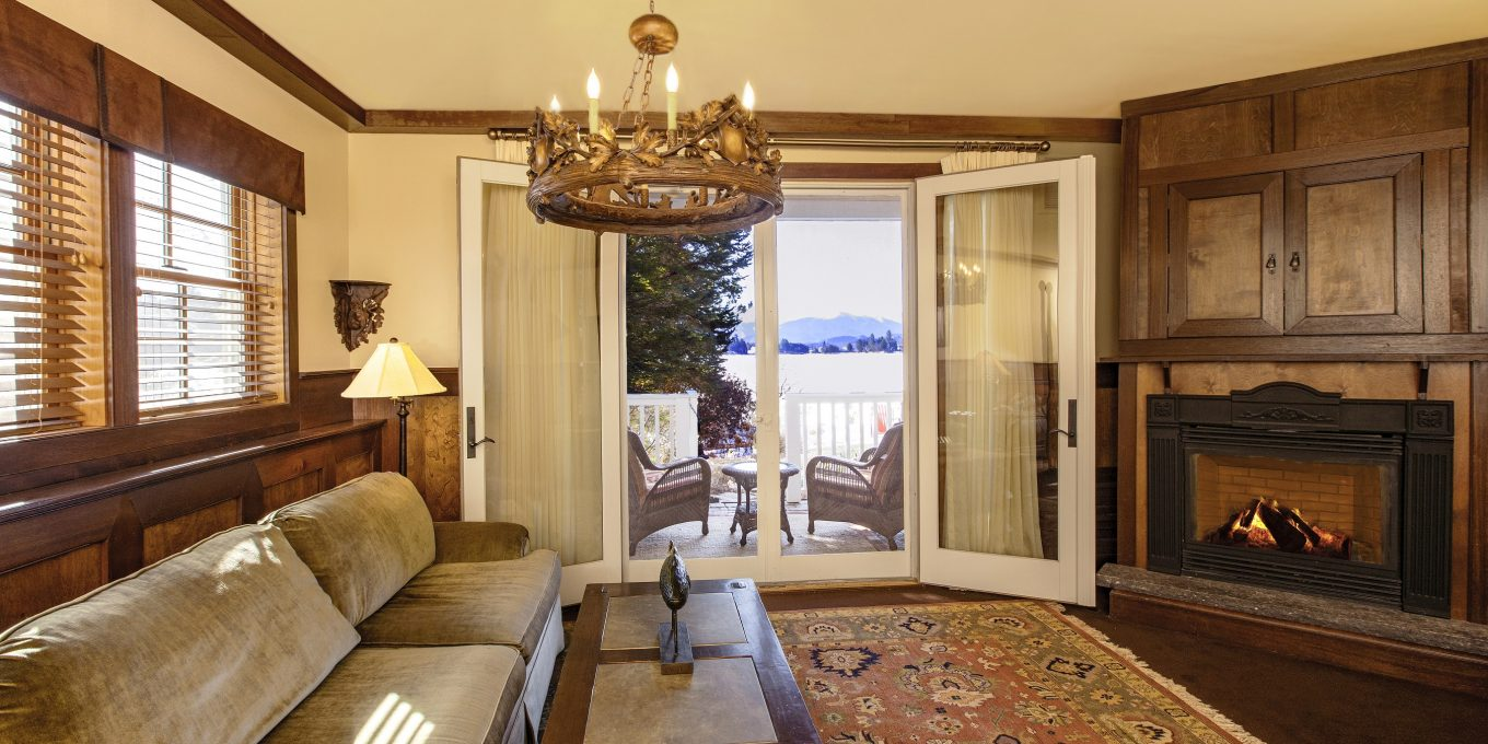 Open french doors to a patio and a fireplace across from a couch and coffee table