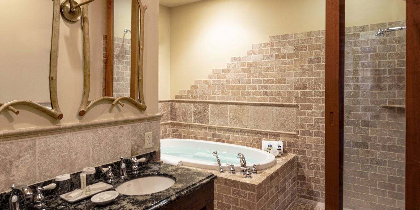A large joint tub and shower area against a wall and double sinks with double mirrors in the Little Whiteface Suite Bathroom