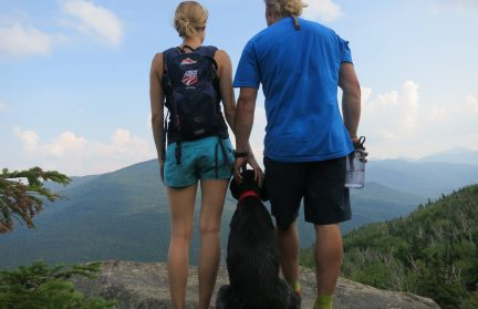Two people standing at a peek during a hike with a dog