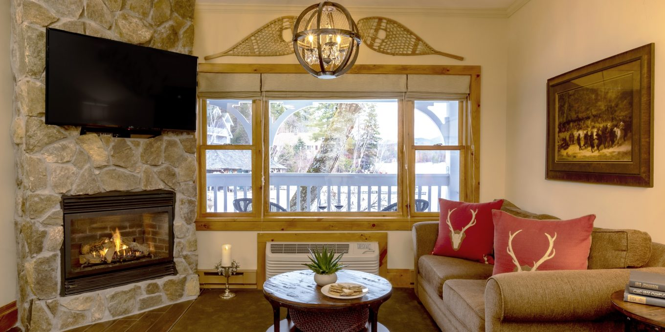 A lit stone fireplace next to a window with a view of a patio and the woods