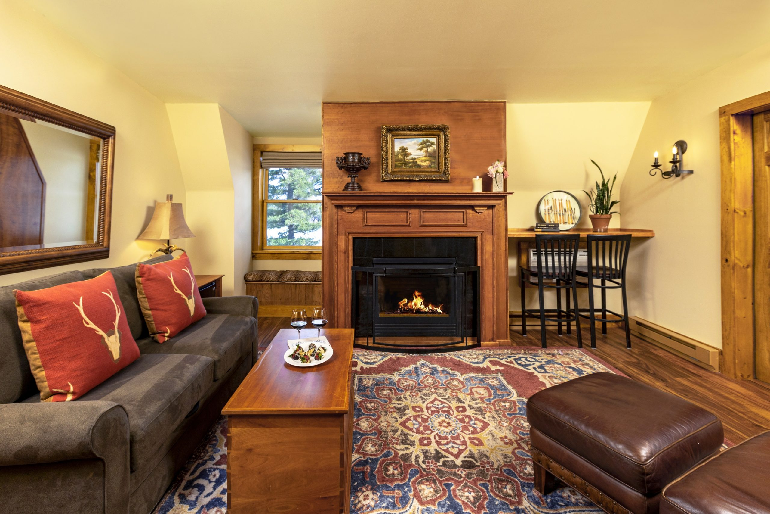 A cozy lit fireplace in the middle of a wall adjacent to a large couch and coffee table