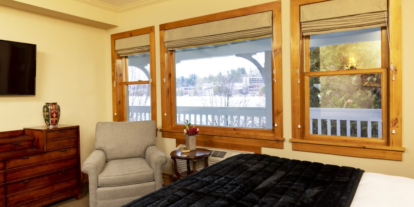 Three separated windows looking out to the patio with an large bed and an arm chair in the room